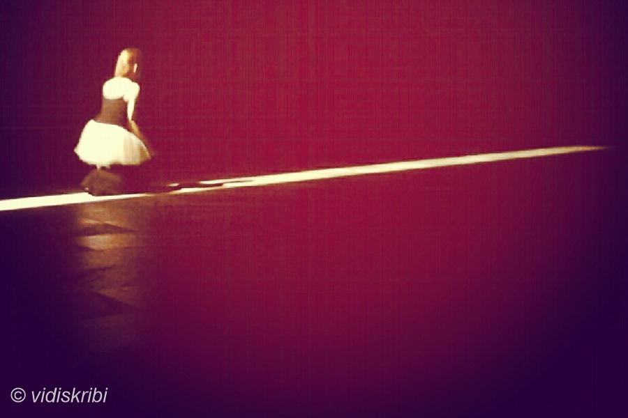 attrice inginocchiata su una lama di luce