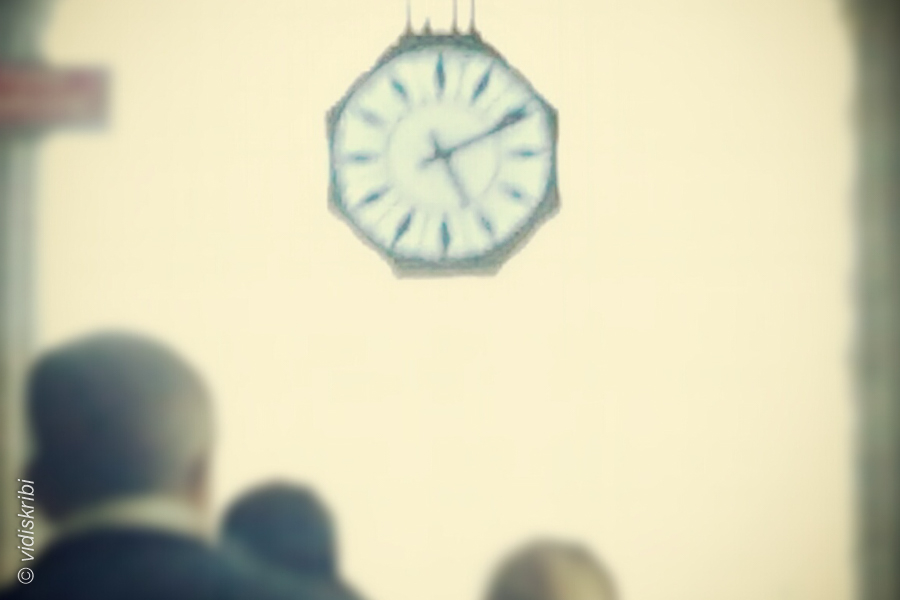 Un orologio e teste di persone
